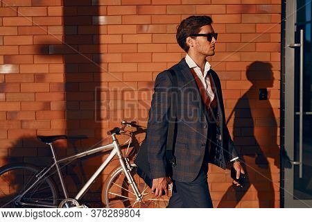 Side View Of Confident Man In Smart Casual Clothes Walking Near Bike And Brick Wall While Commuting