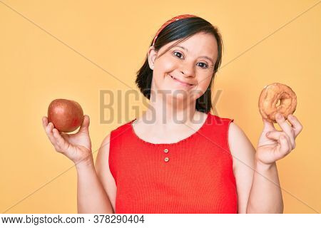 Brunette woman with down syndrome holding red apple and donut sitting smiling and laughing hard out loud because funny crazy joke.