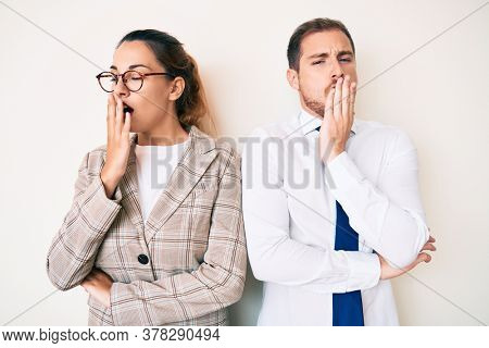 Beautiful couple wearing business clothes bored yawning tired covering mouth with hand. restless and sleepiness.