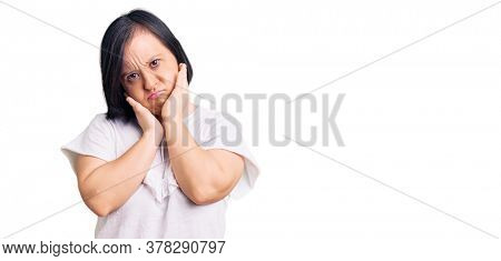 Brunette woman with down syndrome wearing casual white tshirt tired hands covering face, depression and sadness, upset and irritated for problem