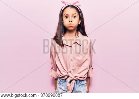 Beautiful child girl wearing casual clothes puffing cheeks with funny face. mouth inflated with air, crazy expression.