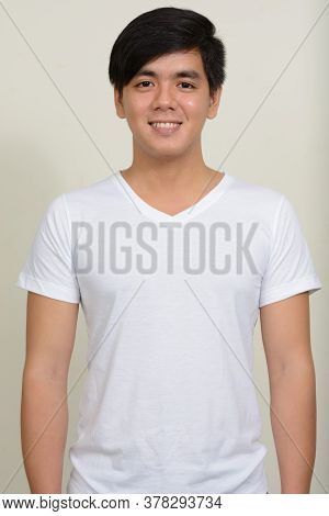 Portrait Of Young Handsome Asian Man Against White Background