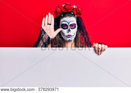 Young woman wearing day of the dead costume holding blank empty banner with open hand doing stop sign with serious and confident expression, defense gesture
