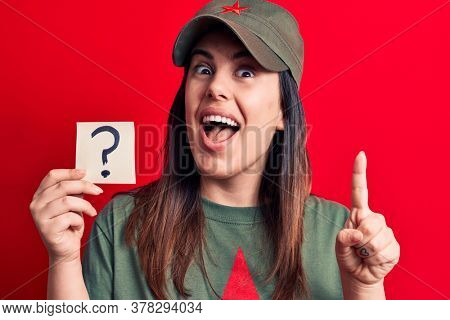 Beautiful woman wearing cap with red star communist symbol holding question mark reminder smiling with an idea or question pointing finger with happy face, number one