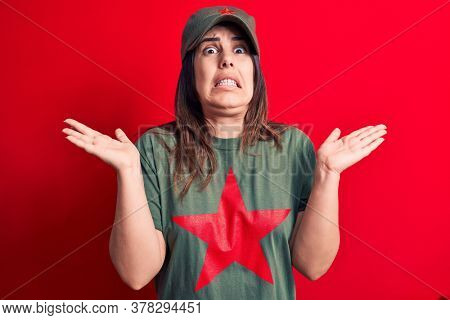 Young beautiful brunette woman wearing cap and t-shirt with red star communist symbol clueless and confused with open arms, no idea and doubtful face.