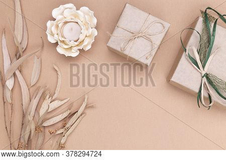 Autumn Composition. Gifts Wrapped In Kraft Paper, Autumn Eucalyptus Leaves, Candle In The Shape Of A
