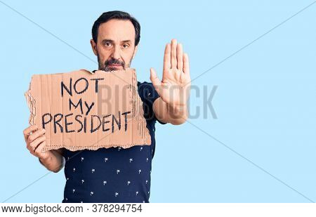 Middle age handsome man holding not my president carboard banner with open hand doing stop sign with serious and confident expression, defense gesture