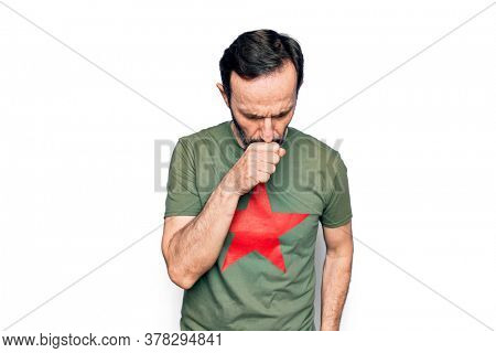 Middle age handsome man wearing t-shirt with revolutionary red star over white background feeling unwell and coughing as symptom for cold or bronchitis. Health care concept.