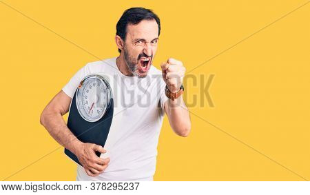 Middle age handsome man holding weighing machine annoyed and frustrated shouting with anger, yelling crazy with anger and hand raised