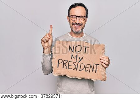Middle age handsome man on disagreement holding banner with not my president message smiling with an idea or question pointing finger with happy face, number one