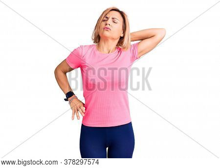 Young blonde woman wearing sportswear suffering of neck ache injury, touching neck with hand, muscular pain