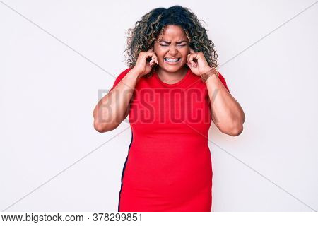 Young african american plus size woman wearing casual clothes covering ears with fingers with annoyed expression for the noise of loud music. deaf concept.