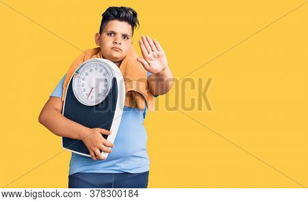 Little boy kid holding weight machine to balance weight loss with open hand doing stop sign with serious and confident expression, defense gesture