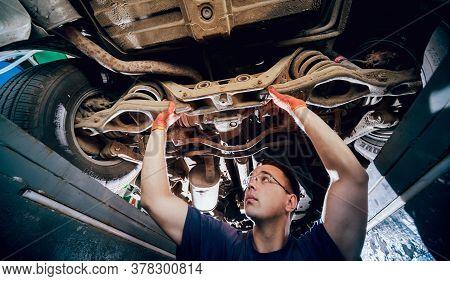 Car Mechanic Repair Car Suspension Of Lifted Automobile