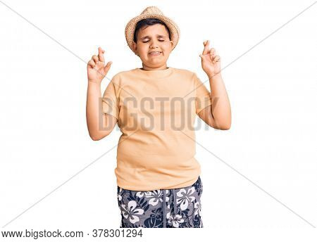 Little boy kid wearing summer hat and hawaiian swimsuit gesturing finger crossed smiling with hope and eyes closed. luck and superstitious concept.