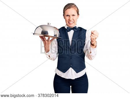 Young beautiful blonde woman wearing waitress uniform holding tray annoyed and frustrated shouting with anger, yelling crazy with anger and hand raised