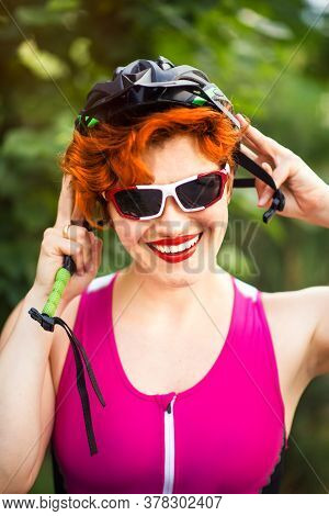 Vertical Portrait Of Sexy Red Haired Smiling Woman Cyclist In Pink Bike Suit And Sun Glasses Wearing