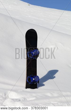 Snowboard In Snowdrift After Snowfall And Snowy Slope For Freeride In Background At Sun Winter Day