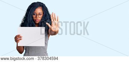 Beautiful african american woman holding blank empty banner with open hand doing stop sign with serious and confident expression, defense gesture