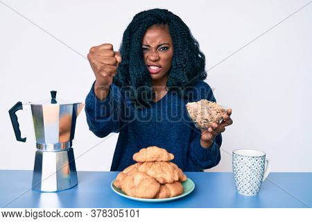 Beautiful african woman sitting on the table eating cereals annoyed and frustrated shouting with anger, yelling crazy with anger and hand raised