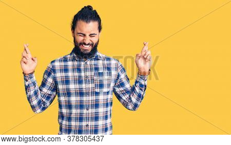 Young arab man wearing casual clothes gesturing finger crossed smiling with hope and eyes closed. luck and superstitious concept.