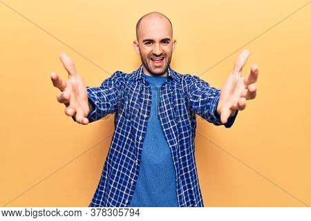 Young handsome bald man wearing casual shirt looking at the camera smiling with open arms for hug. cheerful expression embracing happiness.