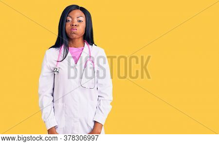 Young african american woman wearing doctor stethoscope puffing cheeks with funny face. mouth inflated with air, crazy expression.