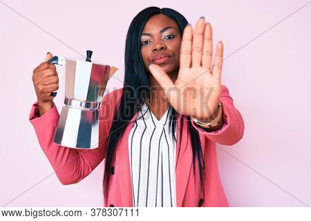 Young african american woman holding italian coffee maker with open hand doing stop sign with serious and confident expression, defense gesture
