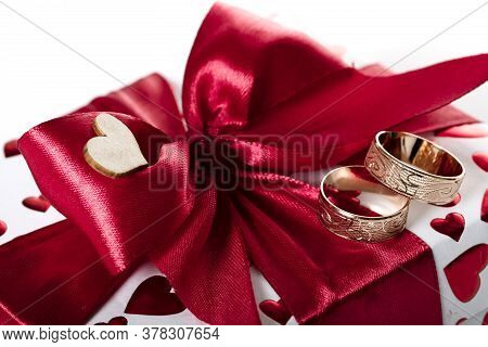 Red Ribbon Tied With A Bow On A Box With A Gift. Close-up.