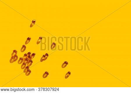 Vitamin D Concept In The Sunlight. Vitamin Gelatin Capsules Scattered On Yellow Background