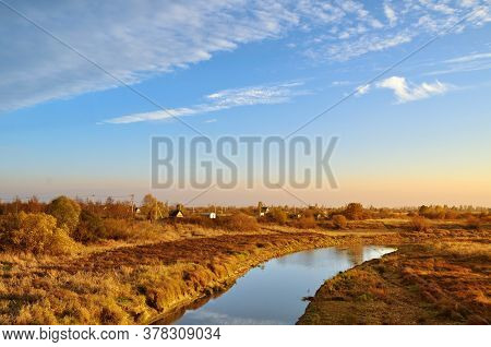 Autumn landscape. Small village at the bank of the river at the autumn evening in bright sunlight - autumn rustic landscape in warm tones. Soft focus processing. Autumn rural landscape