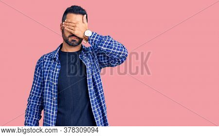 Young hispanic man wearing casual clothes covering eyes with hand, looking serious and sad. sightless, hiding and rejection concept