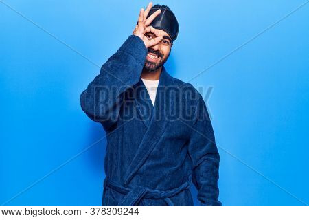 Young hispanic man wearing sleep mask and robe smiling happy doing ok sign with hand on eye looking through fingers