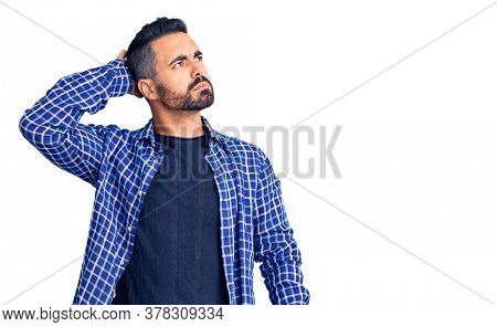 Young hispanic man wearing casual clothes confuse and wondering about question. uncertain with doubt, thinking with hand on head. pensive concept.