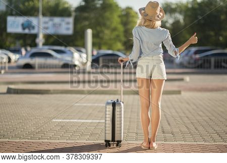 Catch Taxi. Young Woman Wearing Summer Hat, Standing Near Airport And Trying To Stop Car, Full Lengt