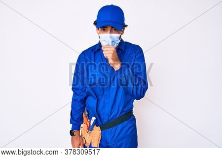 Handsome young man with curly hair and bear wearing handyman uniform and covid-19 safety mask feeling unwell and coughing as symptom for cold or bronchitis. health care concept.