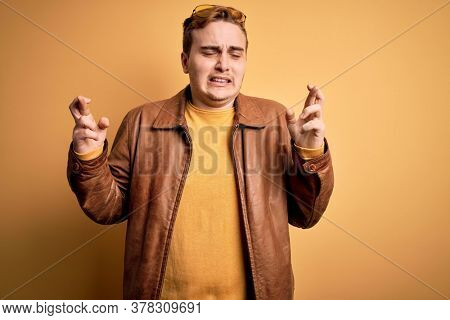 Young handsome redhead man wearing casual leather jacket over isolated yellow background gesturing finger crossed smiling with hope and eyes closed. Luck and superstitious concept.