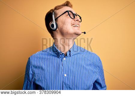 Young handsome redhead call center agent man wearing glasses working using headset looking away to side with smile on face, natural expression. Laughing confident.