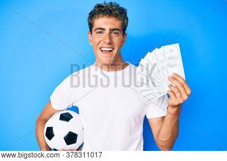 Young handsome man holding soccer ball and dollars banknotes smiling and laughing hard out loud because funny crazy joke.