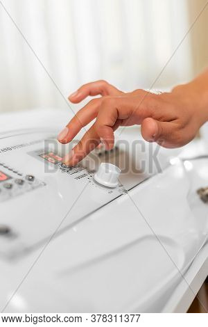 Massage Specialist Womans Hand Adjusts Vacuum Machine For Anti-cellulite Massage. Lipomassage Machin