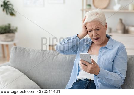 Mobile Scams Concept. Shocked Senior Woman Looking At Smartphone Screen And Touching Head In Frustra