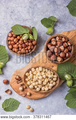 Top View Of Hazelnuts With Peeled Hazelnut And Leaf  In Brown Bowl On Concrete Background. Top View
