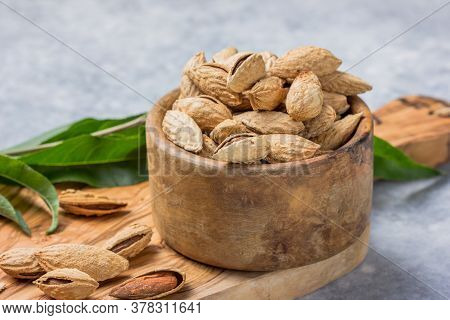 Unshelled Almonds In Bowl With Leaf. Almond. Raw  Almond Petals For Confectionery. Raw  Almond Petal