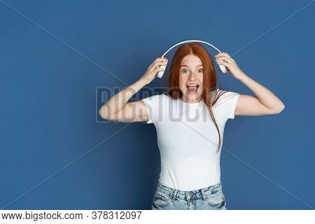 Listen To Music With Headphones. Caucasian Young Girls Portrait On Blue Background. Beautiful Female
