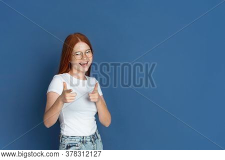 Pointing, Choosing. Caucasian Young Girls Portrait On Blue Background. Beautiful Female Redhair Mode