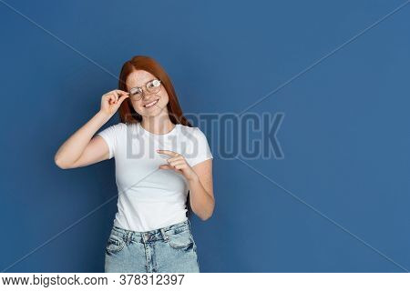 Showing Tiny. Caucasian Young Girls Portrait On Blue Background. Beautiful Female Redhair Model With