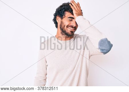 Handsome young man with curly hair and bear wearing casual winter sweater surprised with hand on head for mistake, remember error. forgot, bad memory concept.