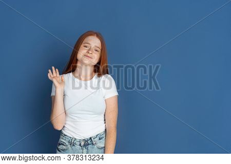 Say Hello. Caucasian Young Girls Portrait On Blue Background. Beautiful Female Redhair Model With Cu