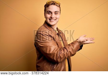 Young handsome redhead man wearing casual leather jacket over isolated yellow background pointing aside with hands open palms showing copy space, presenting advertisement smiling excited happy