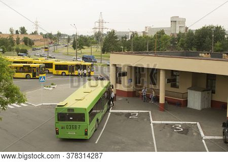 Green And Yellow Buses At The Local Small Suburban Single-decker Bus Station, Passengers Get Into Th